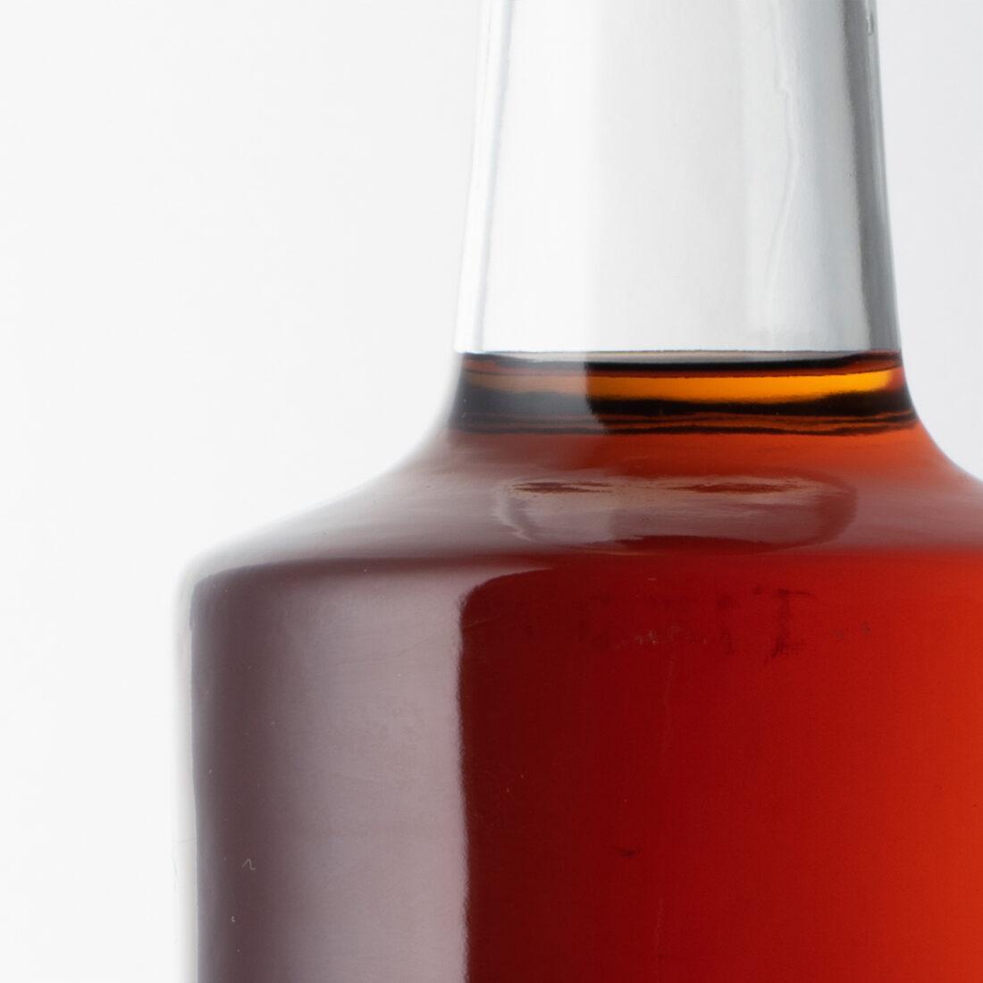 Foto della bottiglia prima dell'intervento in post-produzione: sono presenti alcune imperfezioni dei riflessi date dalle piccole irregolarità del vetro