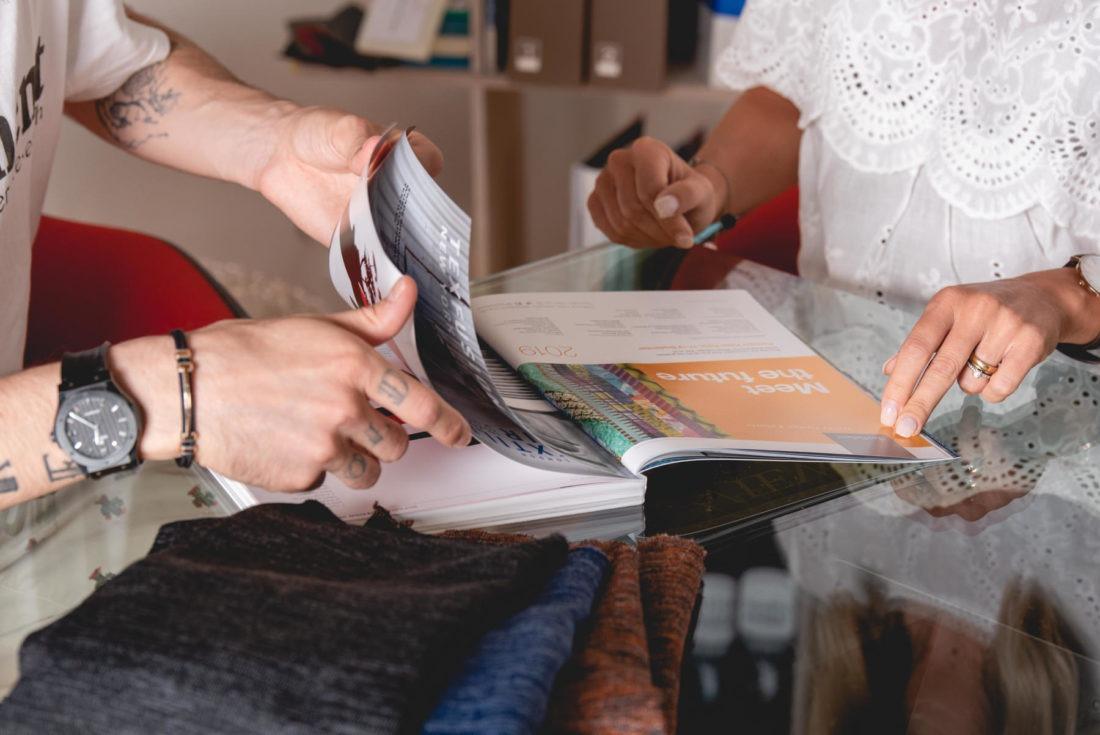 Foto aziendale con due persone che sfogliano un catalogo